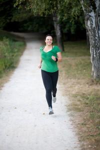 Woman in green tee running trail
